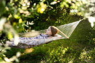 Germany, Bavaria, Landshut, Girl relaxing in hammock in garden - SARF04322