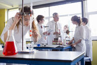 Chemistry teacher guiding high school students conducting scientific experiment - JUIF01958