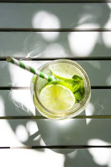Glass of lime-mint lemonade on garden table - LVF08122