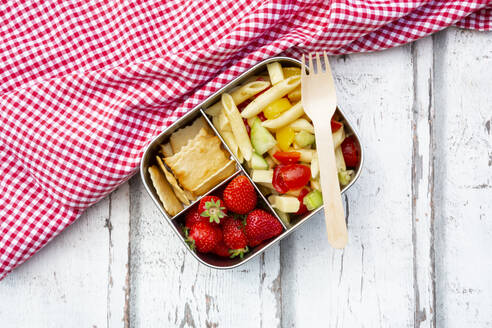 Pasta salad, strawberries and crackers in lunch box on wooden table - LVF08125