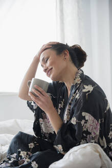 Woman drinking cup of coffee on bed - BLEF08714