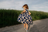 Back view of little girl wearing summer dress with floral design dancing on dirt track - OGF00010