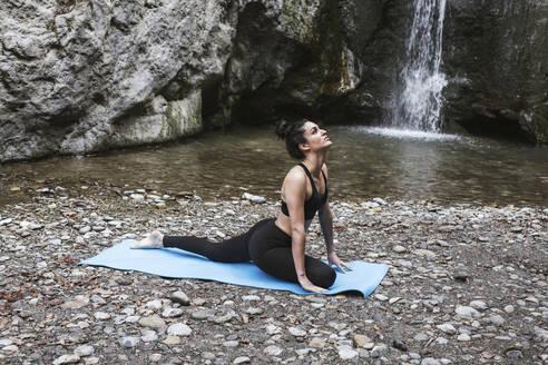 Woman practising yoga at waterfall,  cobra pose - LJF00365