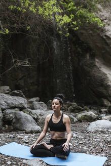 Woman practising yoga meditating at waterfall - LJF00371