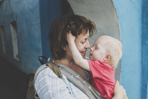 Mother and her little daughter in baby carrier sharing a moment of tenderness, Russia - IHF00171