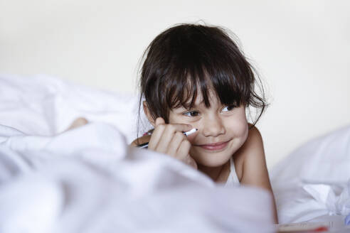 Portrait of smiling little girl lying in bed with felt tip pen - DRF01744
