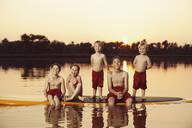 Caucasian children sitting on paddleboard - BLEF08797