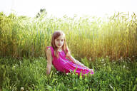 Portrait of young girl wearing vibrant pink dress sitting in front of rye field in summer - LVF08134