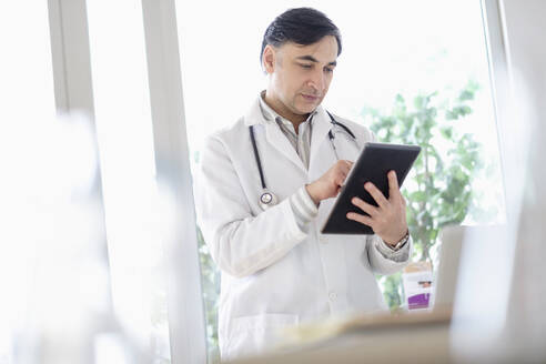 Mixed race doctor using digital tablet - BLEF08845