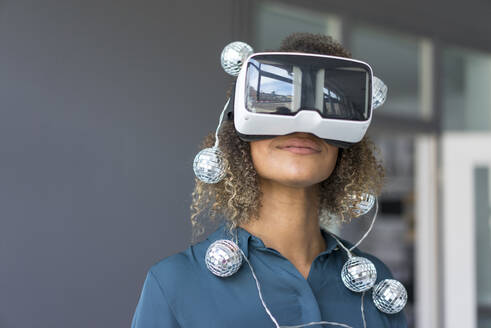Smiling young woman with chain of lights using Virtual Reality Glasses - MOEF02379