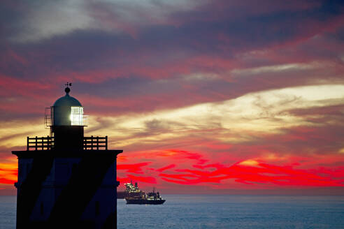Scenic view of lighthouse and ship at sunset - JUIF02180