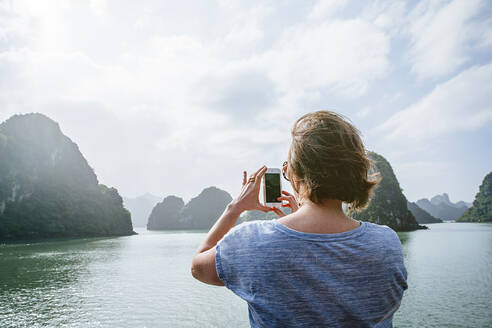 Caucasian woman photographing rock formations in Ha Long Bay, Vietnam - BLEF09021