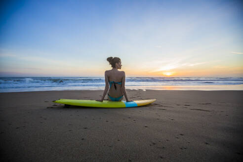 Caucasian woman sitting on surfboard on beach - BLEF09087