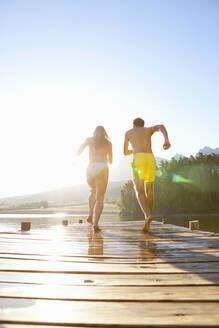 Couple running on wooden dock at lake - JUIF02335