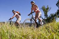 Couple mountain biking in countryside - JUIF02353