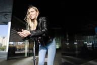 Portrait of blond young woman with smartphone and kick scooter in the city - GIOF06610