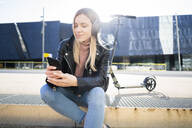 Portrait of young woman listening music with smartphone and headphones, Barcelona, Spain - GIOF06613
