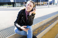 Portrait of young woman listening music with smartphone and headphones, Barcelona, Spain - GIOF06616