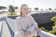 Portrait of smiling blond young woman leaning on railing of footbridge looking at distance - GIOF06649
