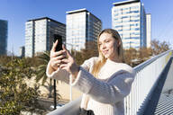 Portrait of blond young woman on footbridge talking selfie with smartphone - GIOF06652