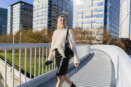 Portrait of blond young woman with smartphone walking on footbridge - GIOF06655