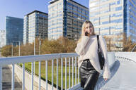 Portrait of blond young woman on the phone walking on footbridge - GIOF06658