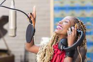 African American singer listening to track in studio - BLEF09247