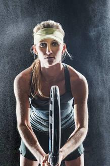 Caucasian tennis player standing in rain - BLEF09289