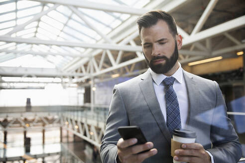 Businessman with coffee using smart phone on office atrium balcony - HEROF36933