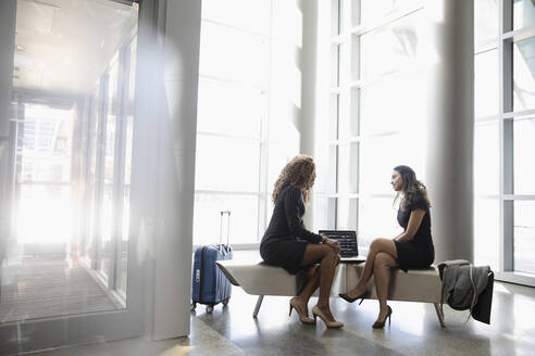 Businesswomen meeting, using laptop in office lobby - HEROF37062