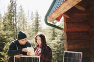 Couple using digital tablet, installing solar panels outside cabin - HEROF37122