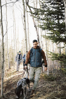 Man with dog hiking in woods - HEROF37134