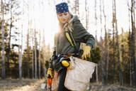 Female volunteer planting trees in woods - HEROF37158