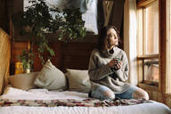 Serene woman with coffee relaxing on cabin bed - HEROF37164