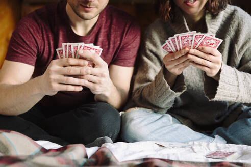 Couple playing cards on bed - HEROF37167