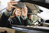 Woman with camera phone riding in car - HEROF37191