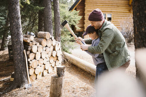 Father teaching son how to cut firewood outside cabin - HEROF37206