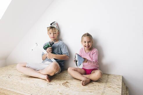 Wickede, NRW, Deutschland. Geschwister spielen mit Werkzeuge in einem renovierten Haus - KMKF00994