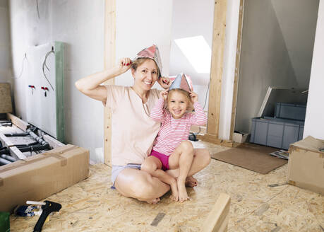 Happy mother and daughter wearing paper hats in a home to be renovated - KMKF00997