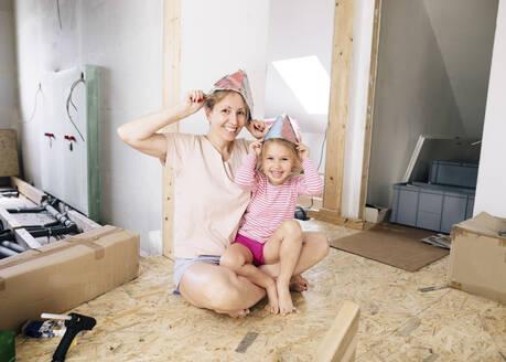 Wickede, NRW, Deutschland. Lachende Mutter und Tochter spielen zusammen in einem renovierten Haus, tragen Hut aus Papier - KMKF00997