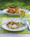 Close up of roasted chicken in lemon sauce outside in garden on table - PPXF00206