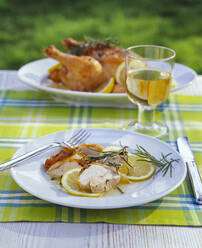 Roasted chicken in lemon sauce and glass of white wine on garden table - PPXF00206