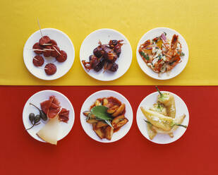 Variety of tapas on plates served on Spanish flag - PPXF00212