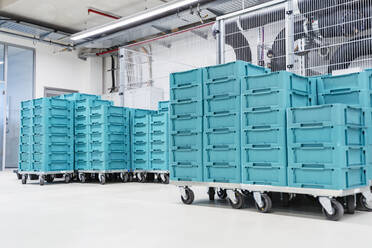 Turquoise colored containers inside modern factory warehouse, Stuttgart, Germany - DIGF07196