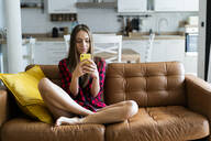 Young woman using cell phone on a couch at home - GIOF06672