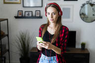 Portrait of young woman with cell phone and headphones at home - GIOF06687