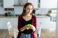 Portrait of young woman with cell phone and headphones at home - GIOF06690
