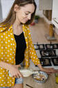 Young woman preparing breakfast on kitchen counter at home - GIOF06696