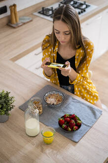 Young woman taking cell phone picture of her breakfast at home - GIOF06705