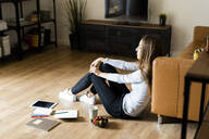 Relaxed young woman sitting on the floor at home having a break - GIOF06717
